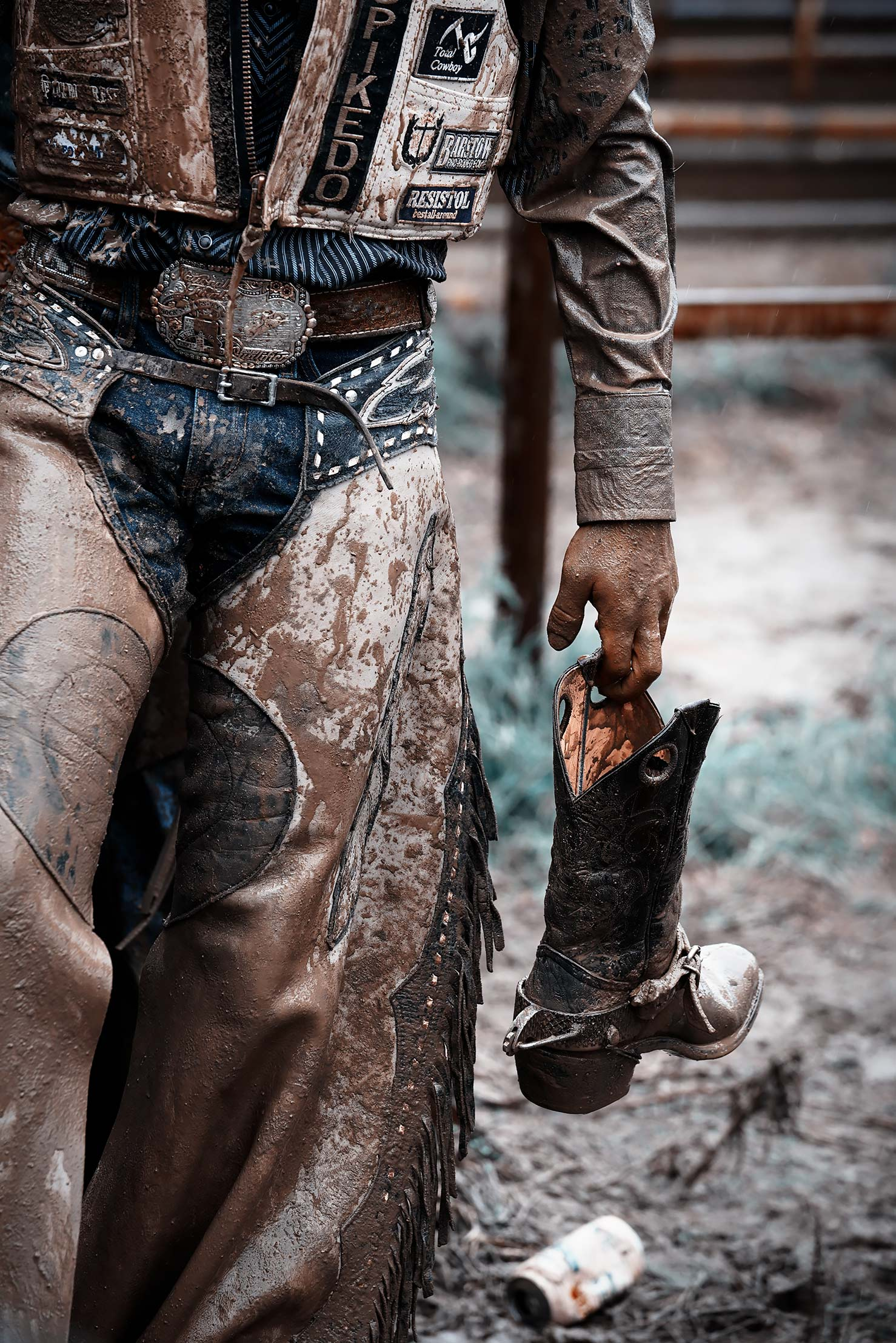 Cowboy holding his muddy boot