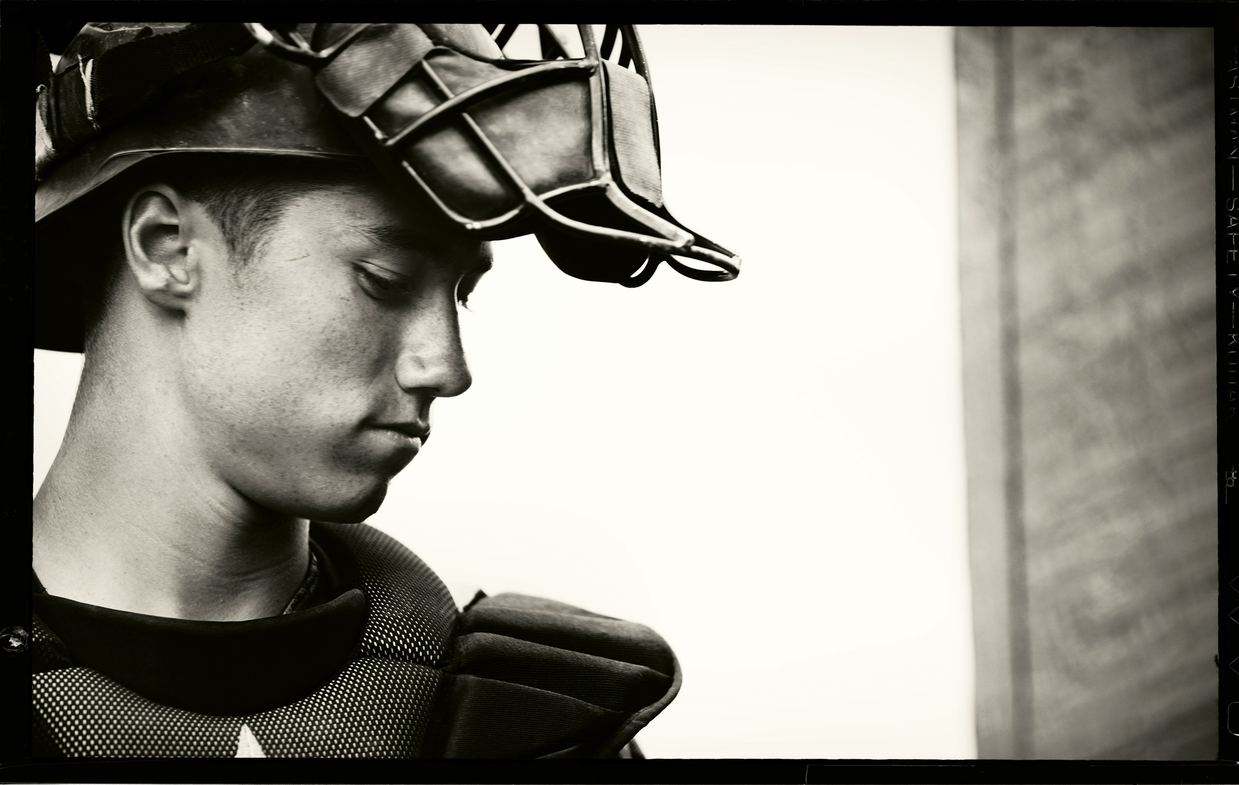 Black and white image of a teenage baseball player wearing his catchers gear