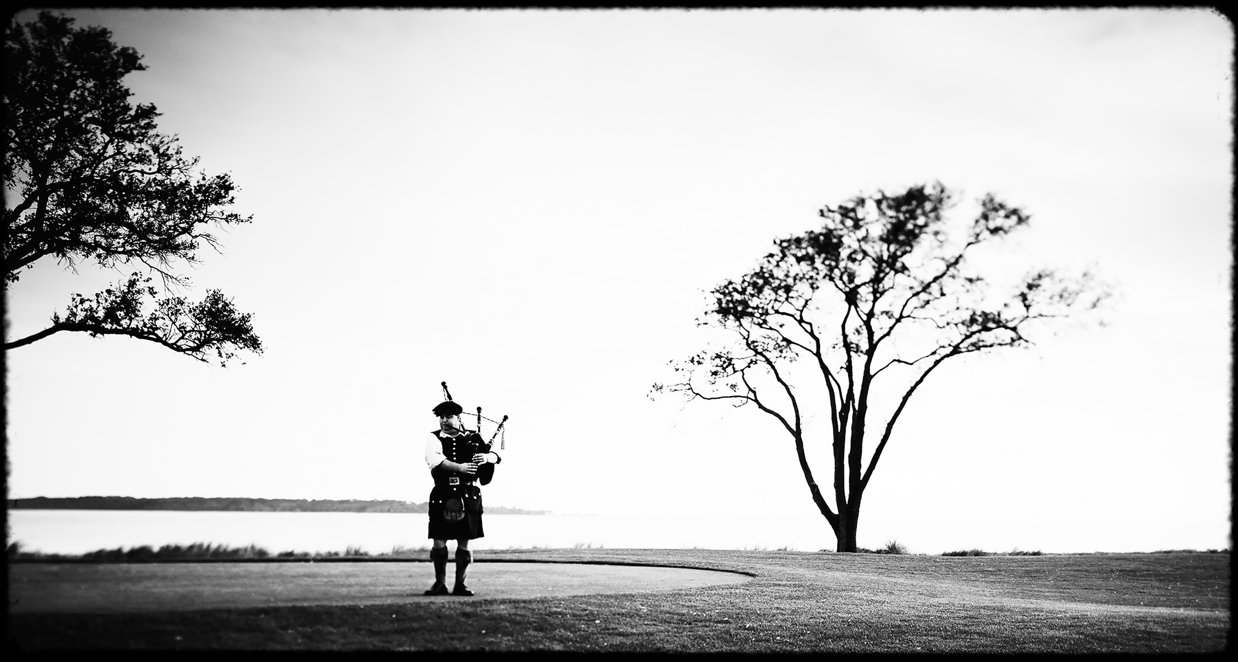 Bagpiper playing the bagpipes on the 18th green at a golf course in Sea Island, Georgia