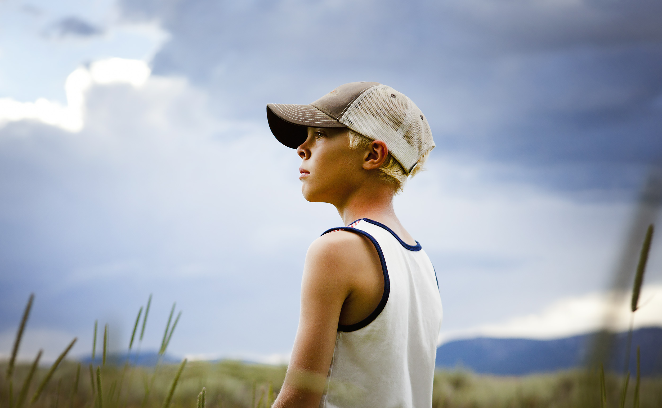 A boy standing in a meadow and looking off in the distance