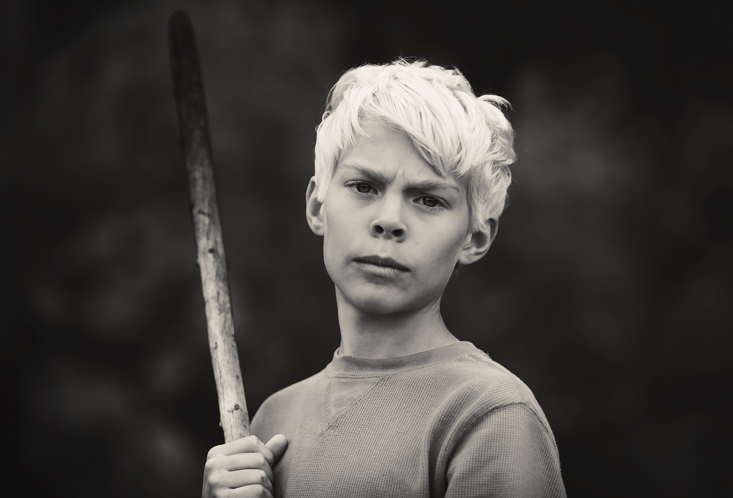 Black and white portrait of a young boy holding a stick