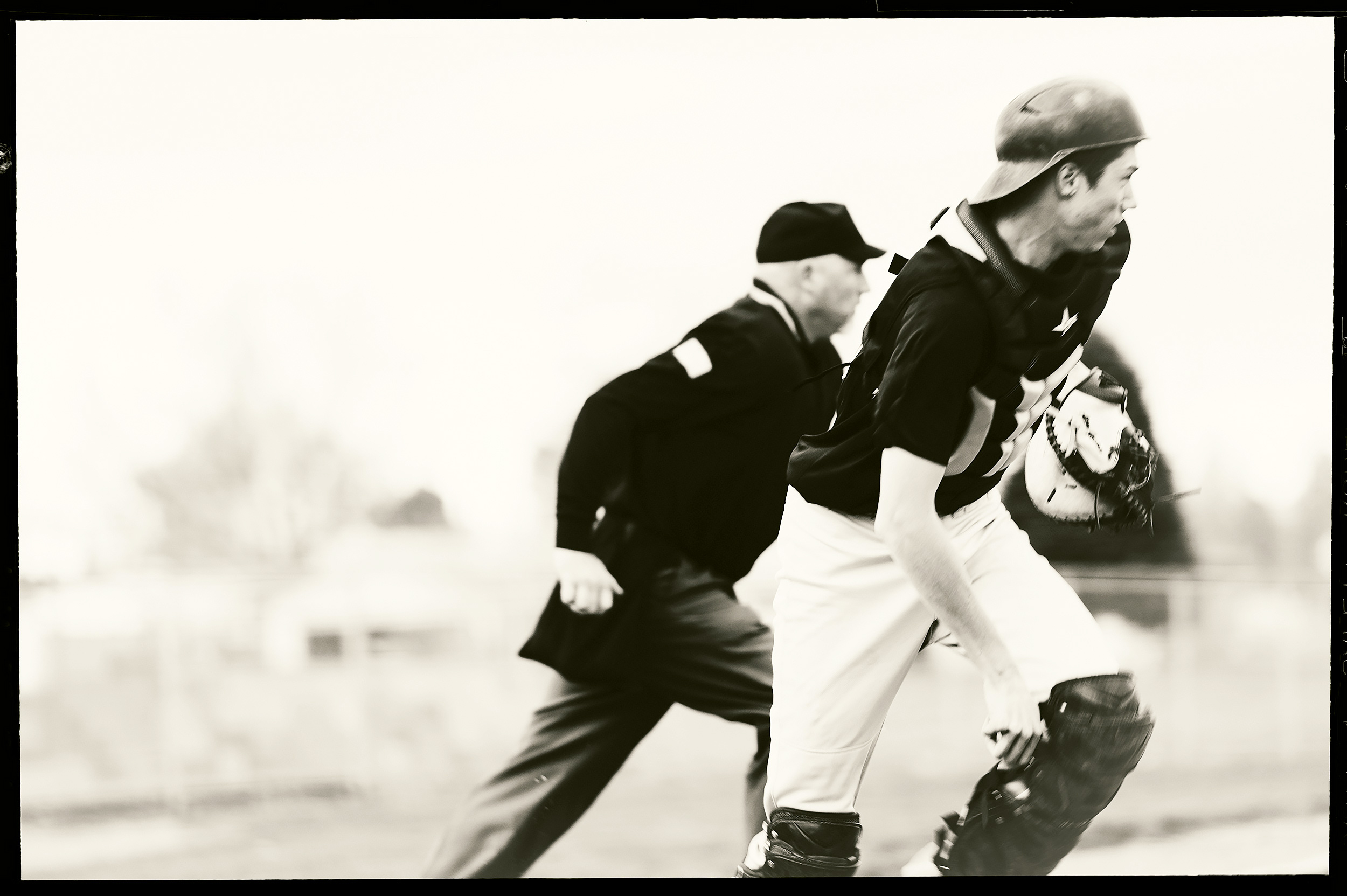 Black and white image of a teenage baseball playing catcher and running alongside the umpire