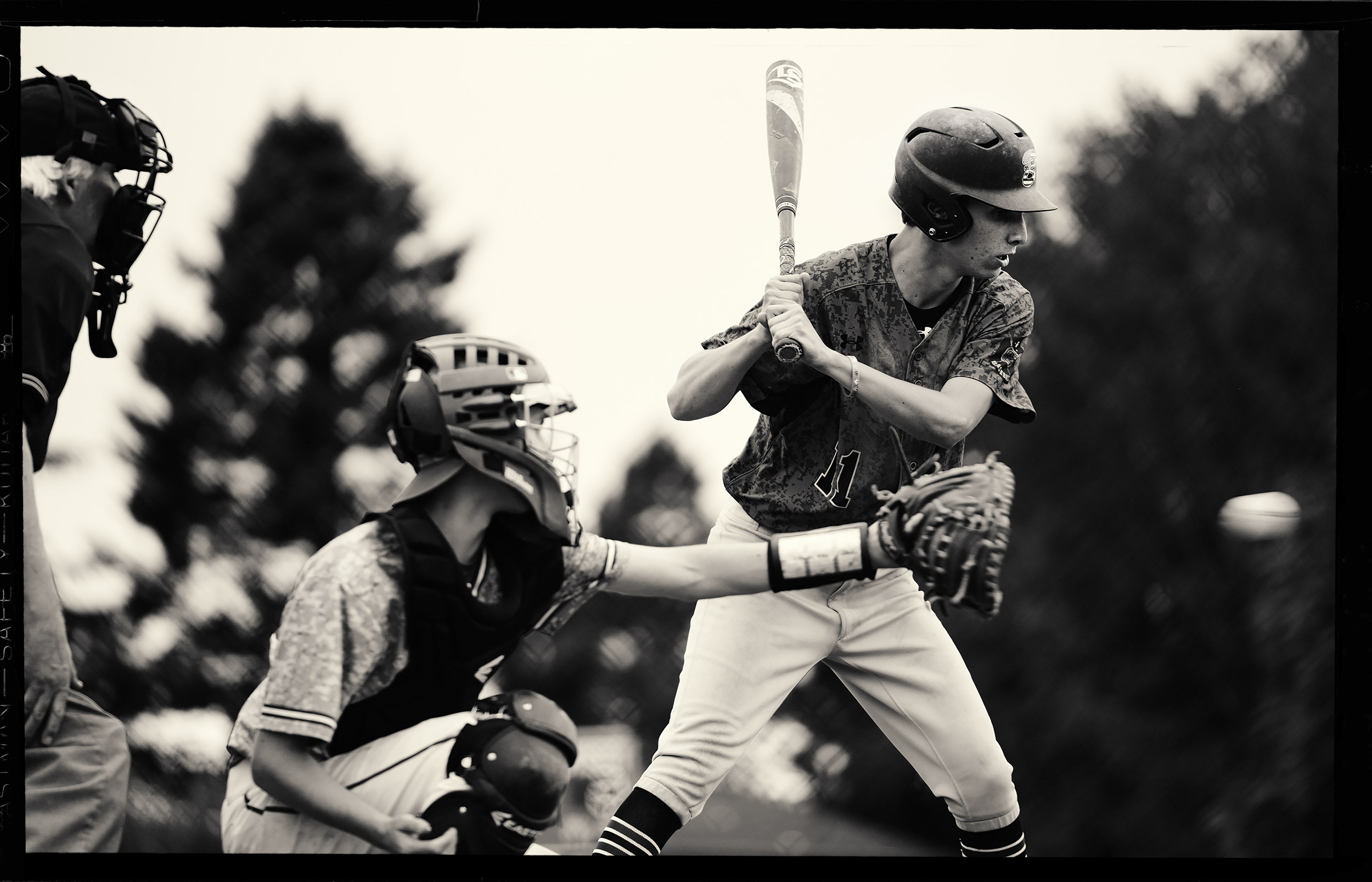 Black and white image of a teenage baseball player standing in the batters box and looking at a fastball