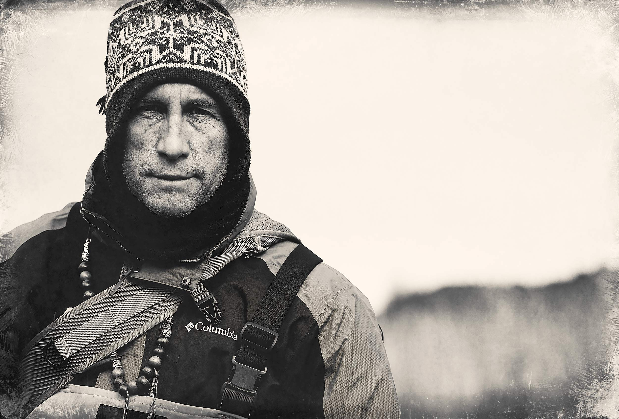 A portrait of a fly fisherman wearing winter clothing and looking at the camera
