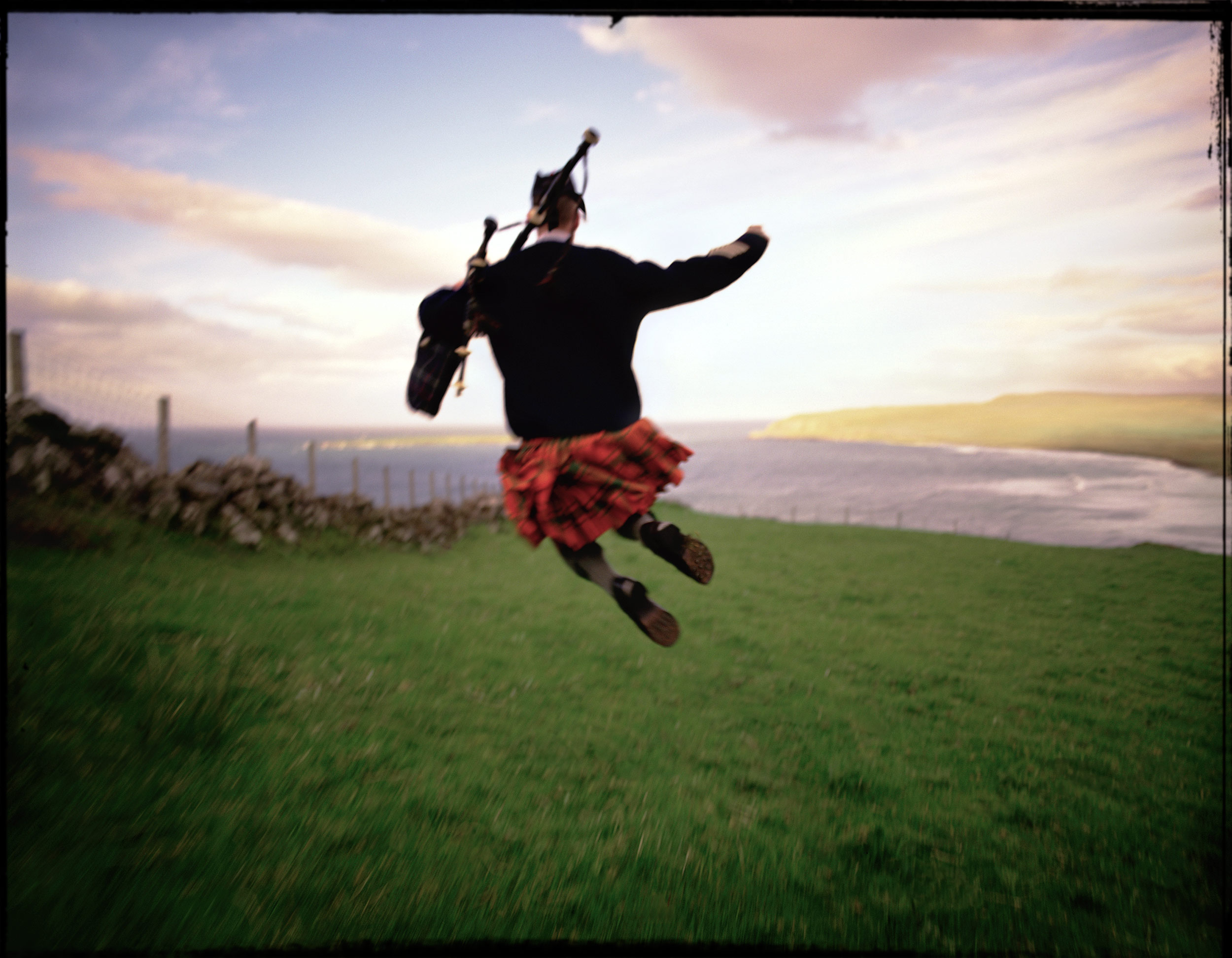 Bagpiper jumping in the air in a green pasture on the Isle of Skye, Scotland