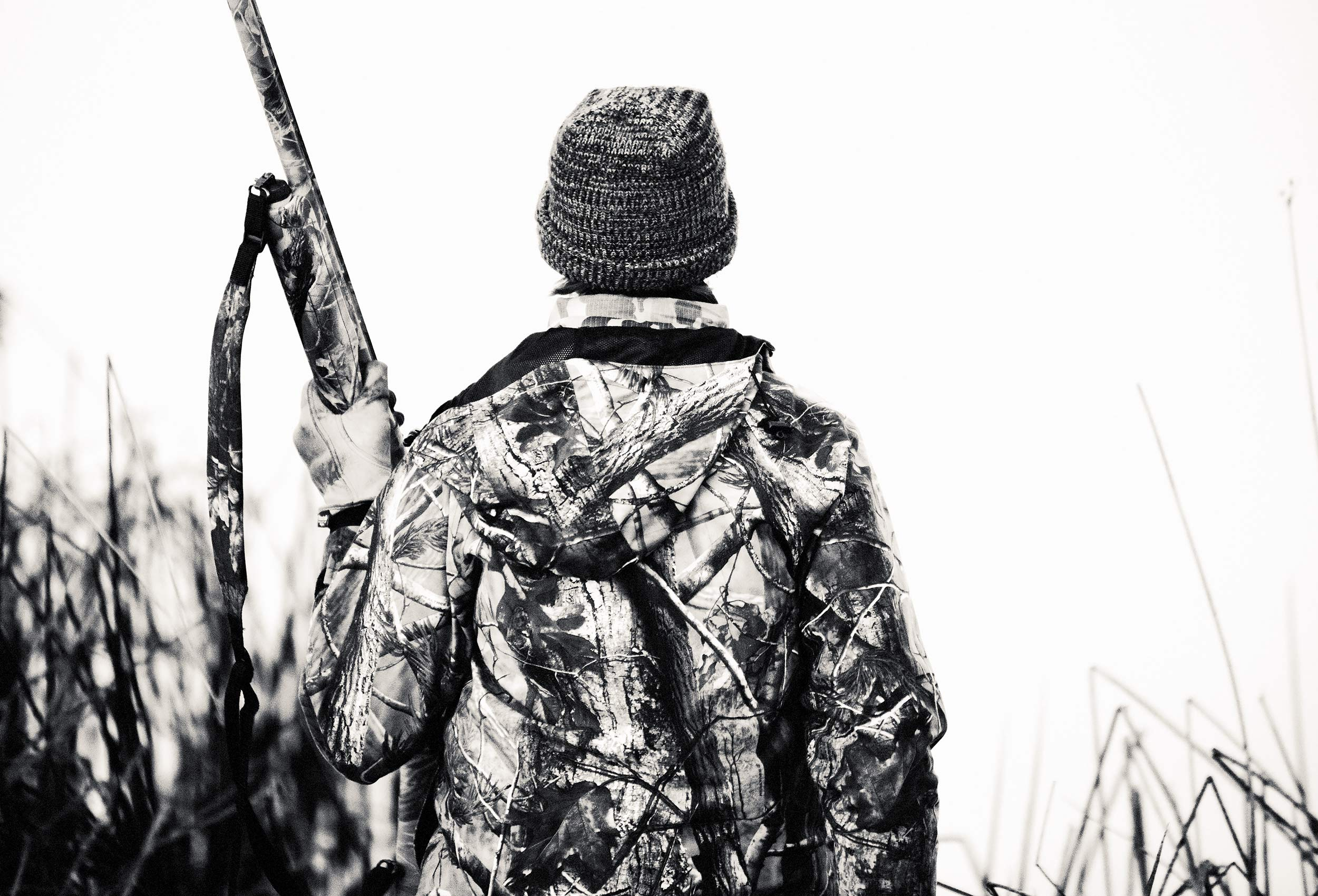 Black and white image of a young duck hunter standing with his shotgun in a duck blind