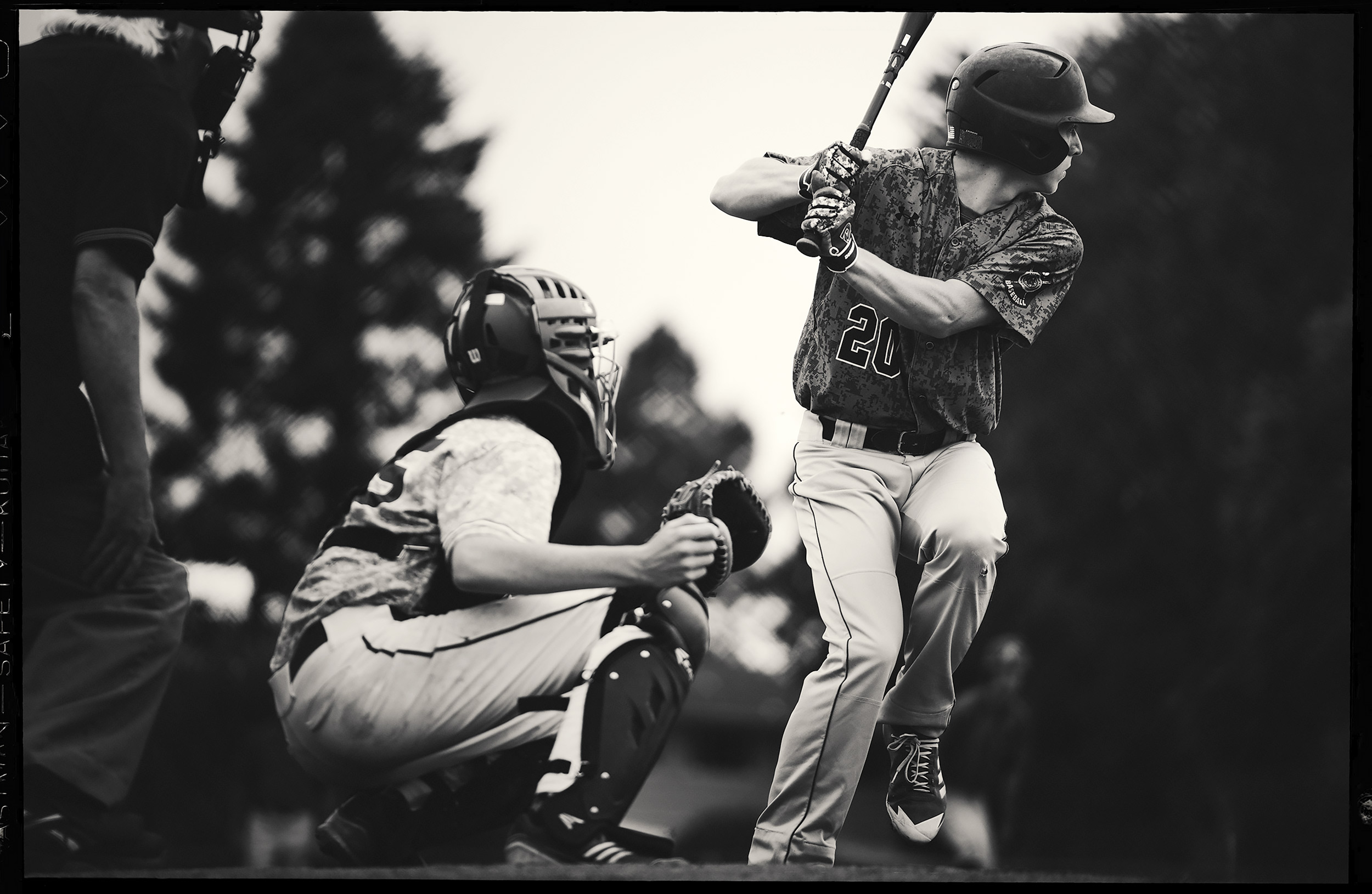 Black and white image of a teenage baseball player standing in the batters box and loading up at a pitch