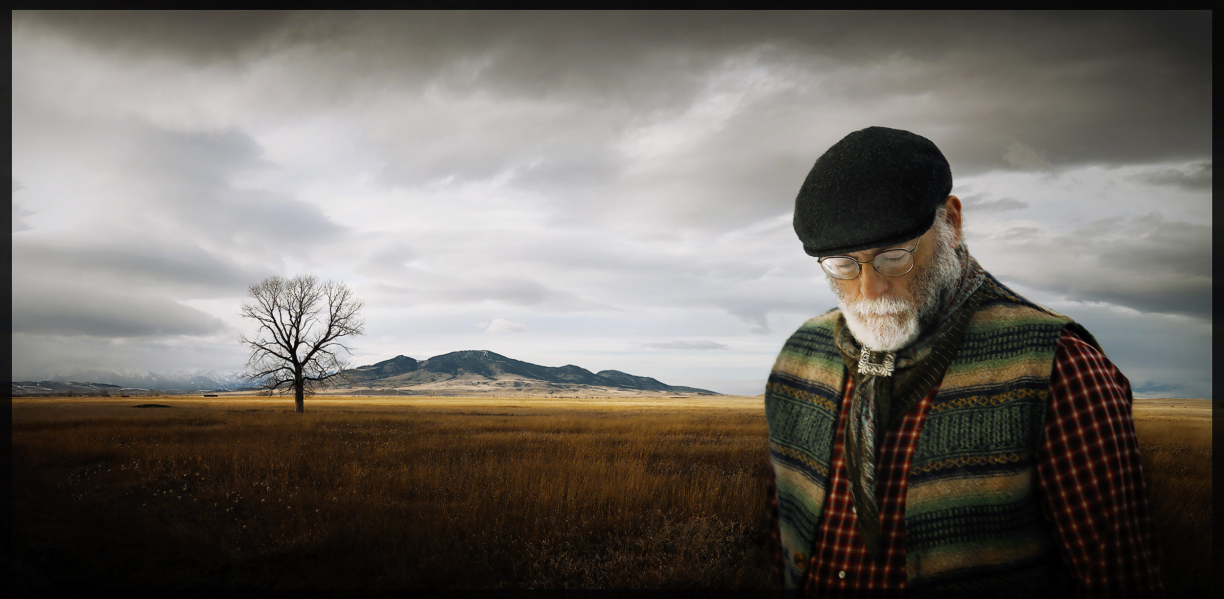 Old hippie with a gray beard standing in a landscape in Montana