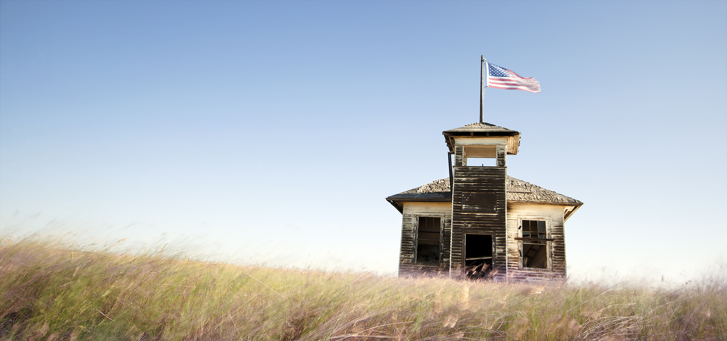 Old schoolhouse with a flag flying on the Hi-Line in Montana