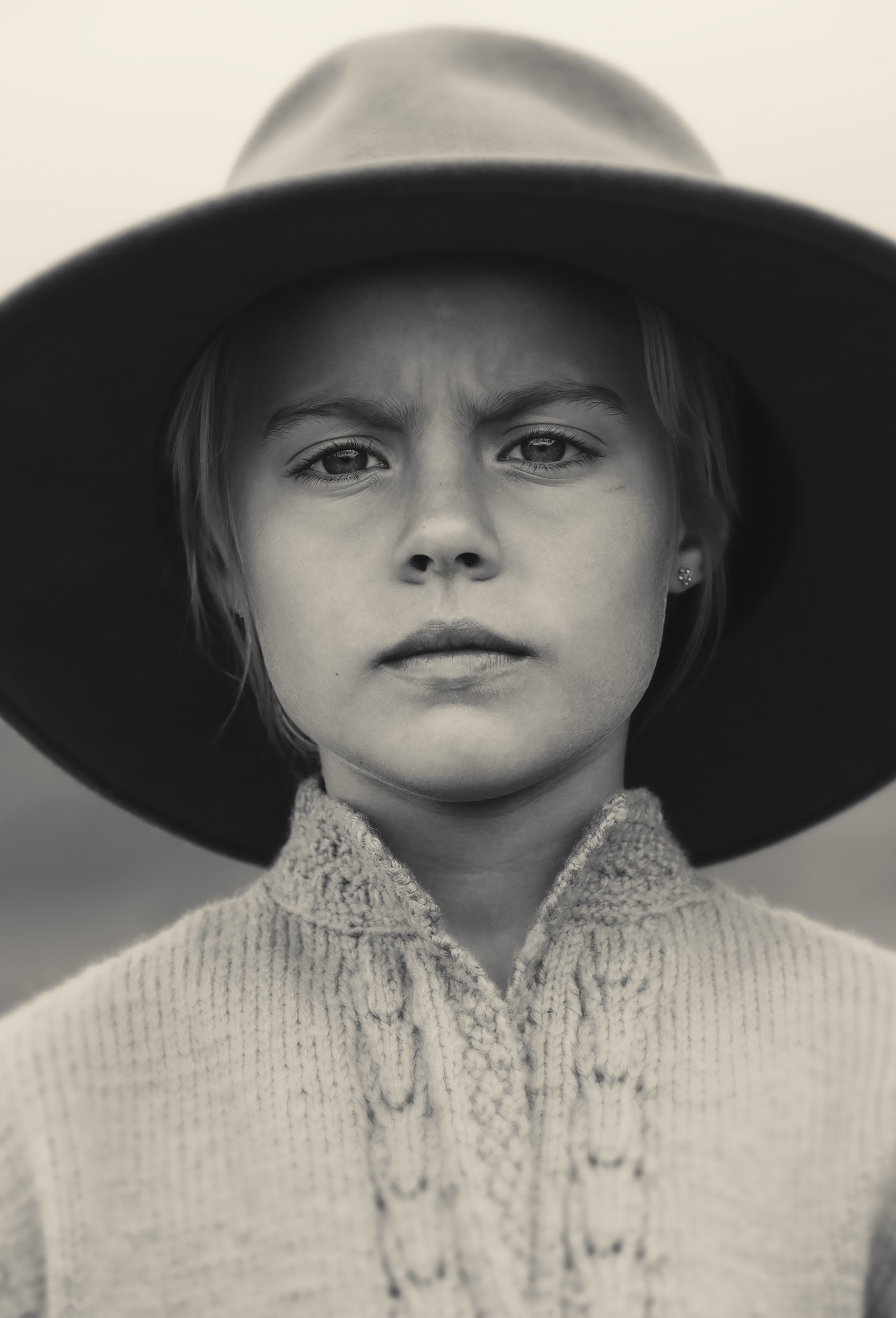 Young cowgirl wearing a cowboy hat looking at camera