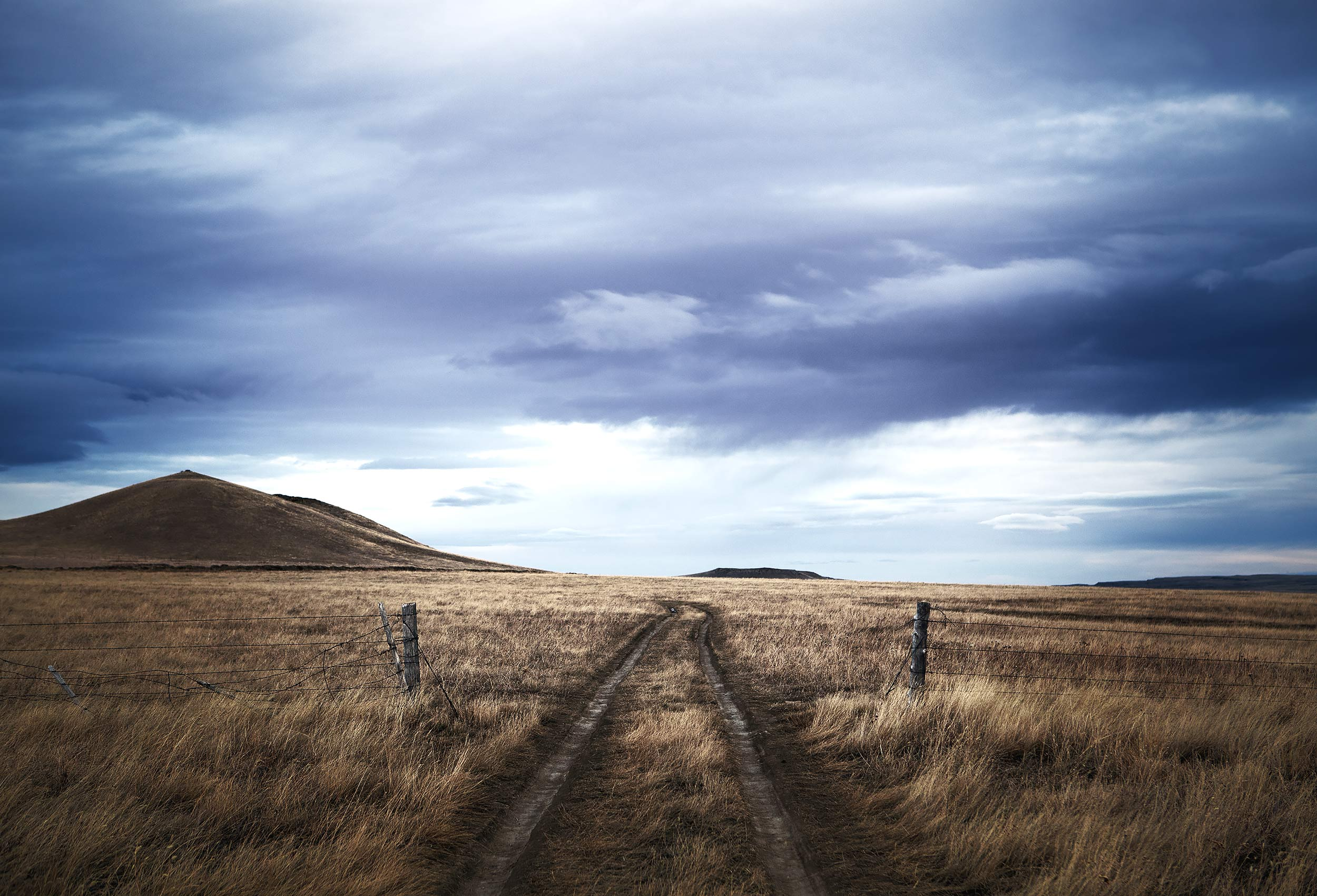 Dirt road ruts on a Montana ranch under a moody blue sky