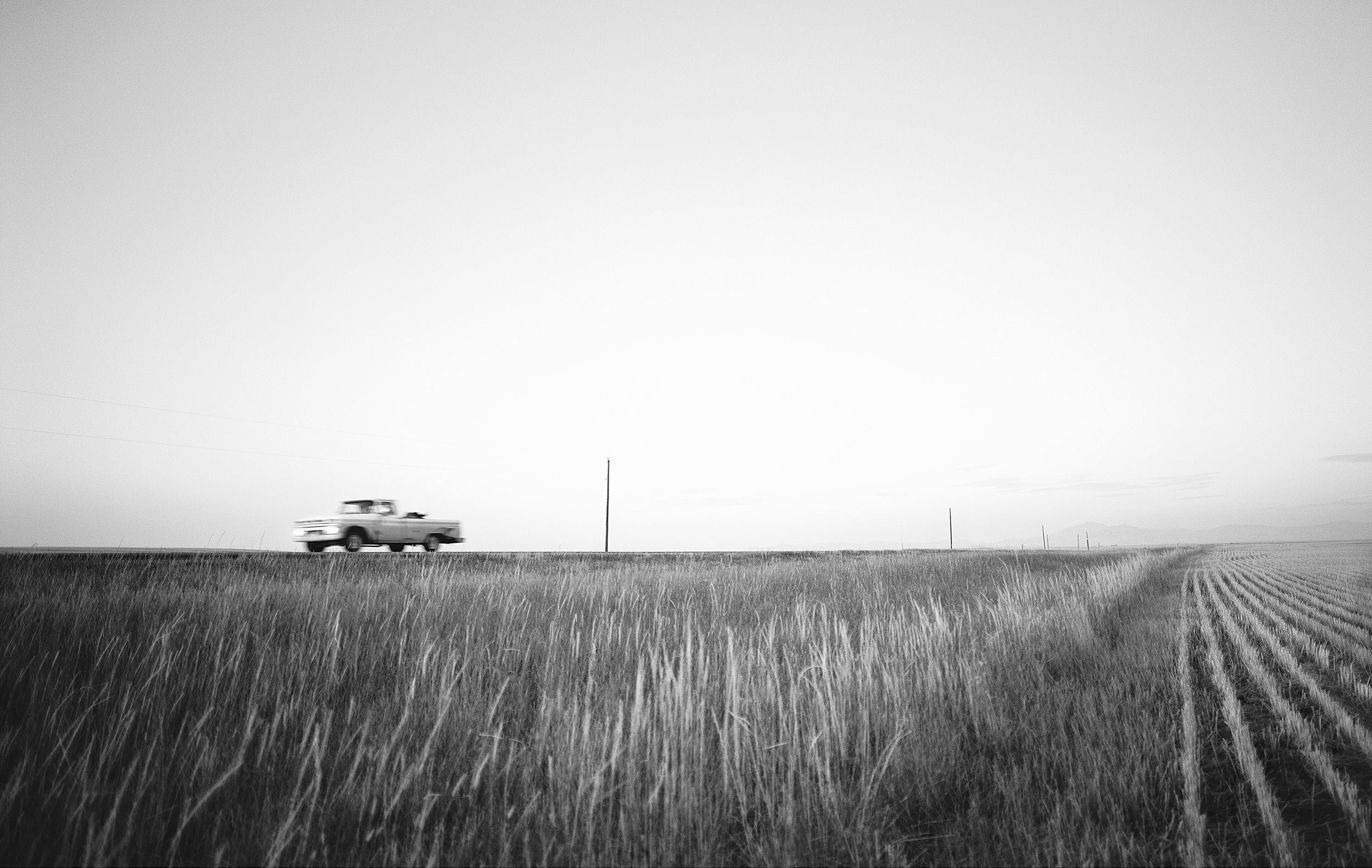Truck driving along a cut hayfield near Lewistown, Montana
