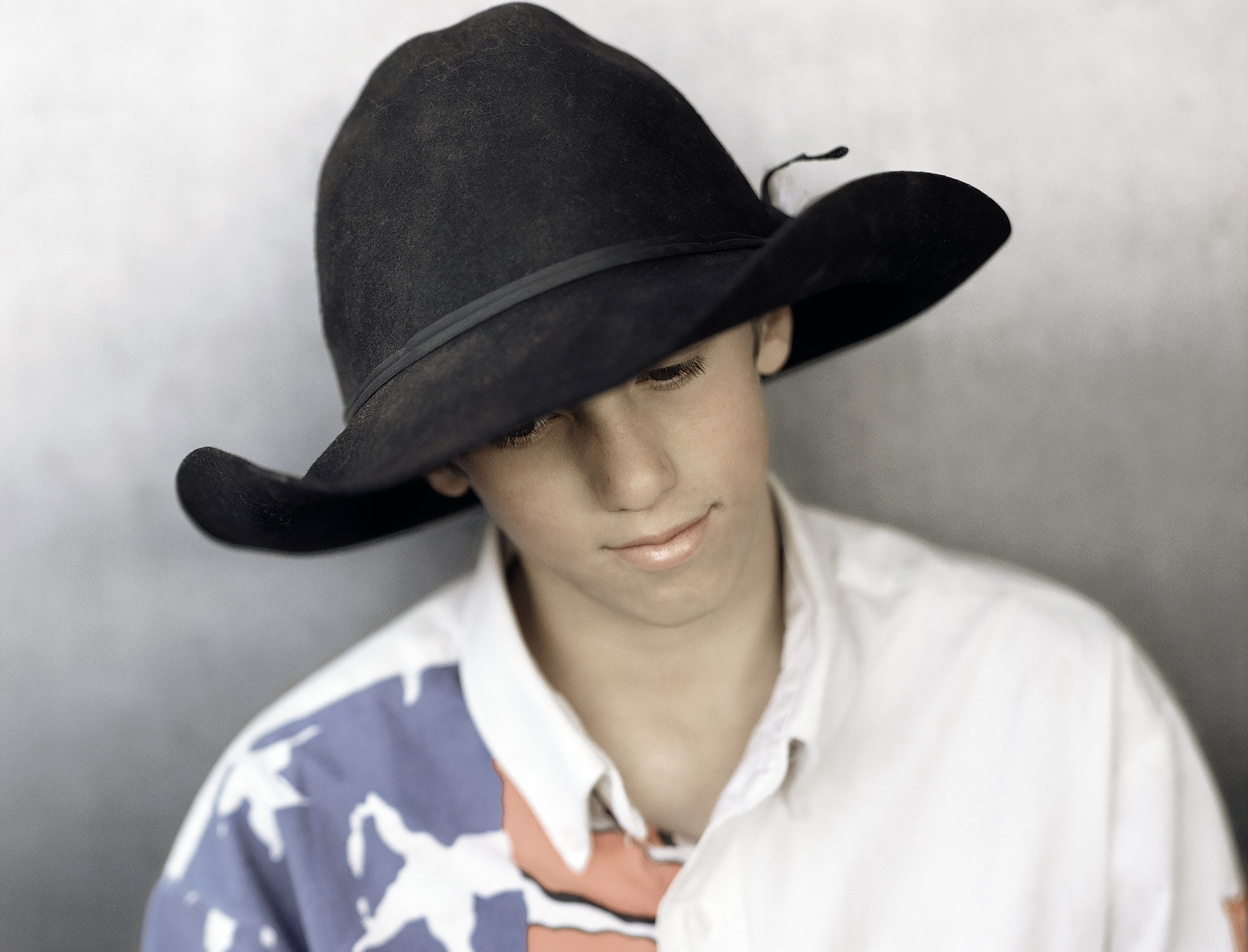Portrait of a young cowboy wearing a black cowboy hat and a patriotic western shirt
