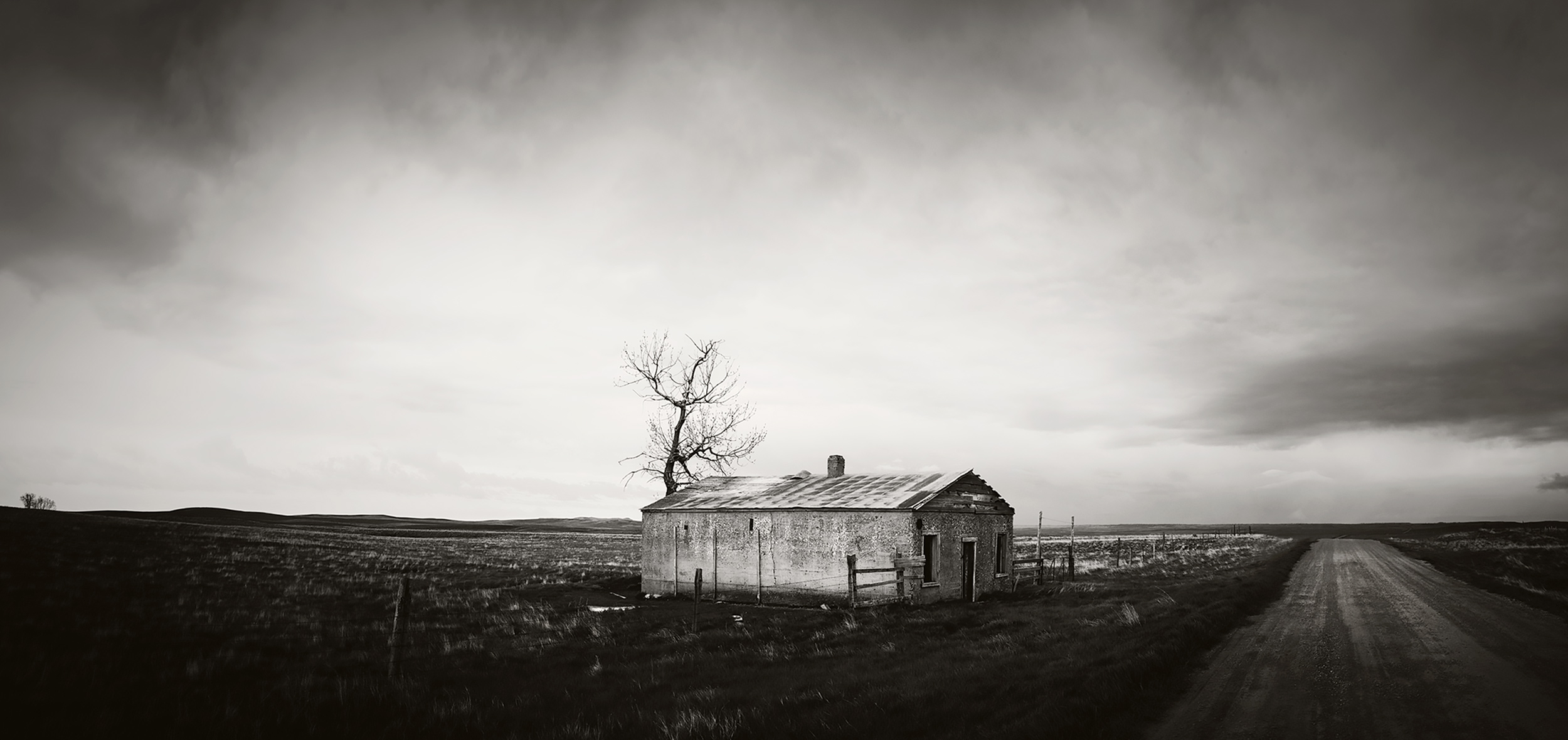 Black and white image of a lone homestead in Central Montana