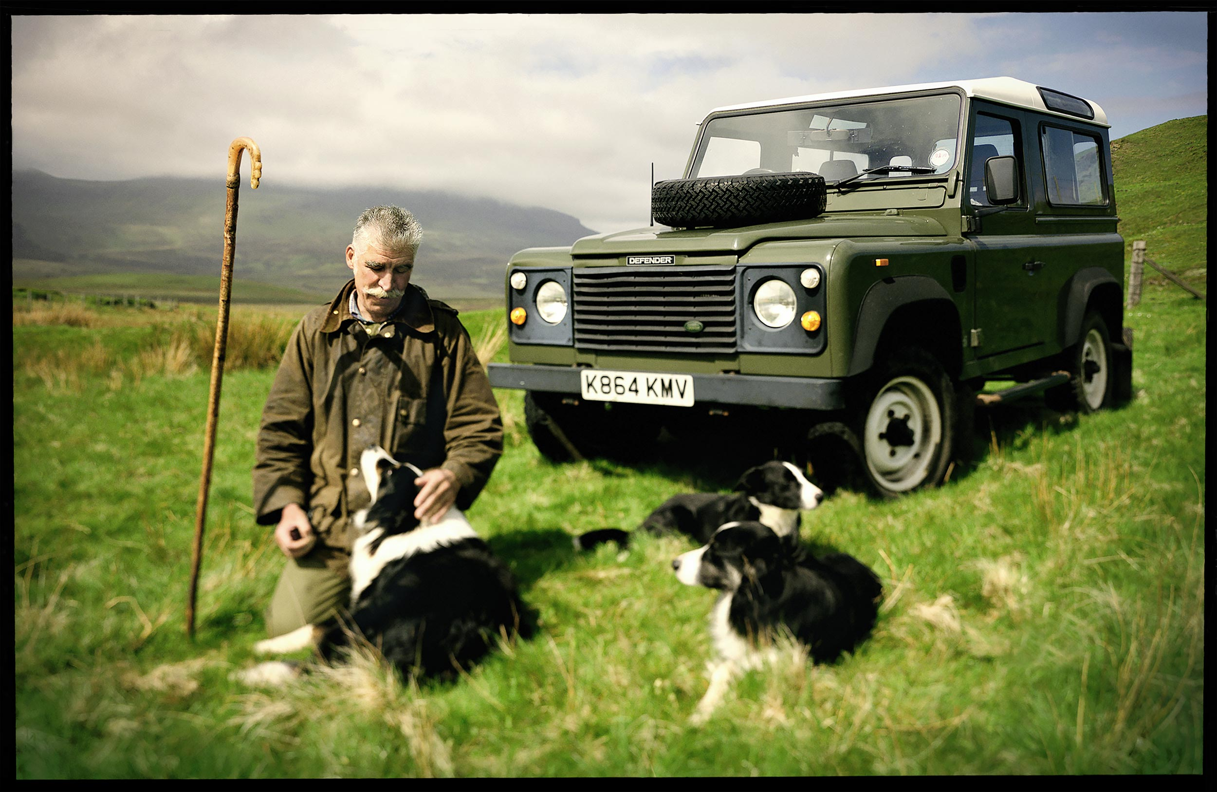 Scottish herdsman with his dogs in a pasture on the Isle of Skye