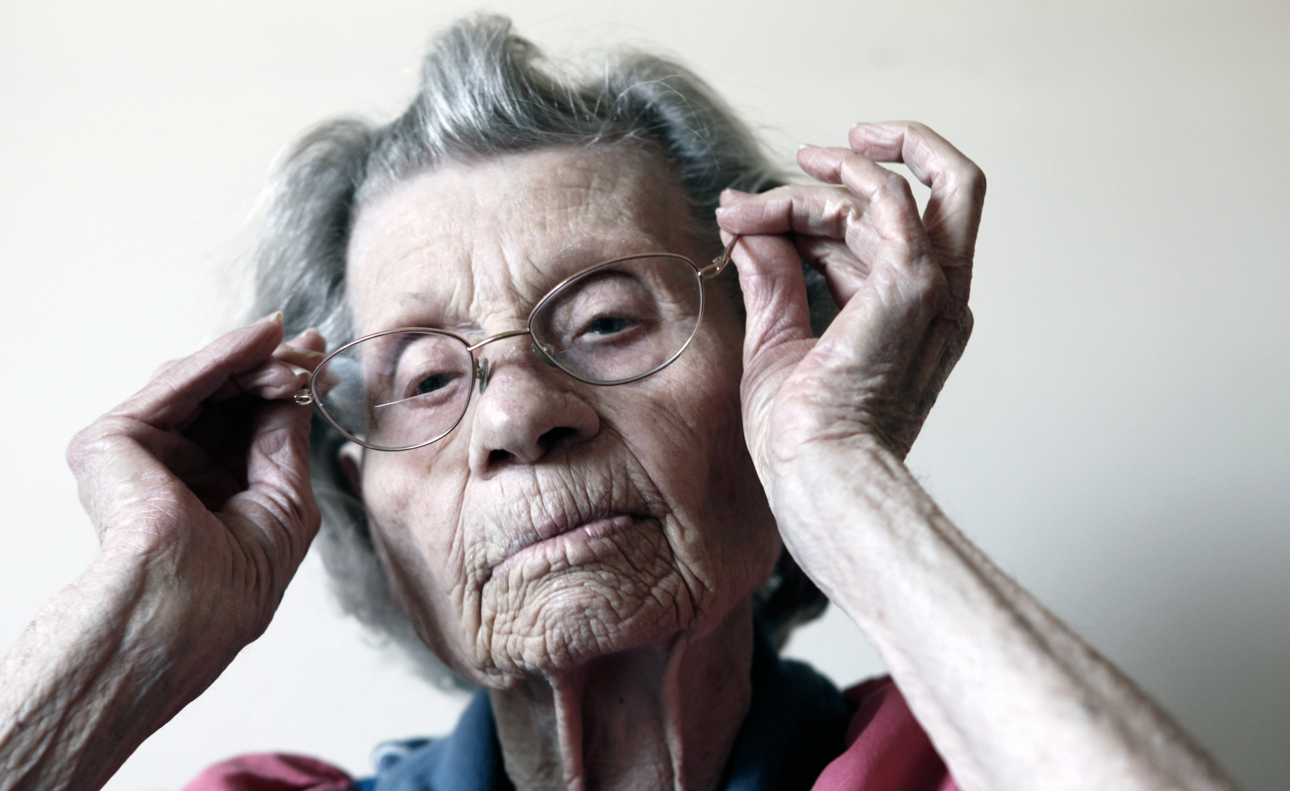 Elderly woman adjusting her glasses - AARP