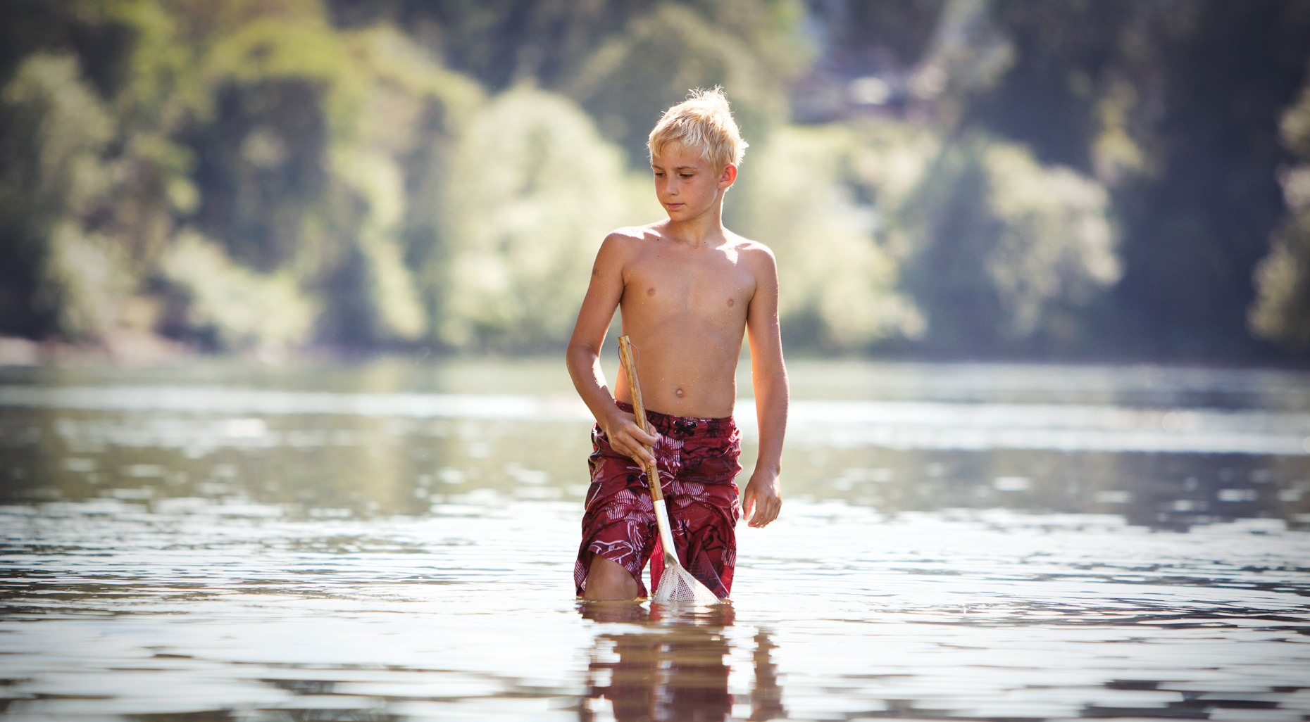 Boy standing knee deep in the Umpqua River